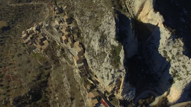 Aerial footage recorded with drone flying over a stunning old town over the cliff with amazing landscape and rock formations in the Catalan Pyrenees during winter travel vacations.
