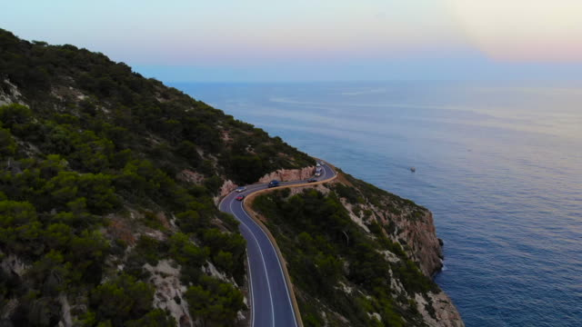 aerial footage recorded with drone flying over a traffic road in the coast with cliffs. - küstenlandschaft stock-videos und b-roll-filmmaterial