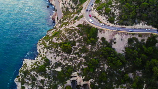 Aerial footage recorded with drone flying over a traffic road in the coast with cliffs.