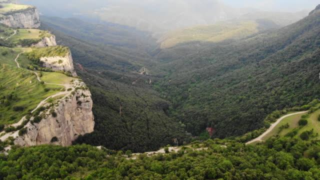 vídeos de stock e filmes b-roll de aerial footage recorded with drone flying over stunning green canyon landscape. - desfiladeiro