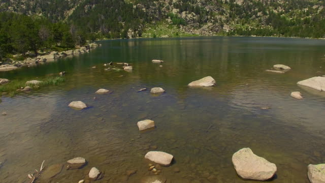 Aerial footage recorded with drone flying over the beautiful lakes in the Catalan Pyrenees high mountains on summer. 4K UHD.