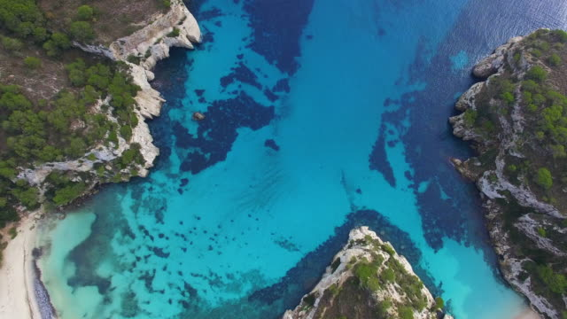 aerial footage recorded with drone flying over the beautiful menorca island beach of cala macarella with beautiful turquoise water in a paradise and peaceful place. 4k uhd. - balearic islands stock videos and b-roll footage