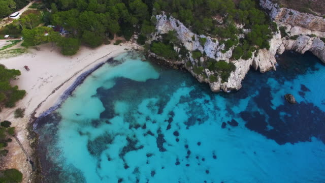 vídeos de stock e filmes b-roll de aerial footage recorded with drone flying over the beautiful menorca island beach of cala macarella with beautiful turquoise water in a paradise and peaceful place. 4k uhd. - baía
