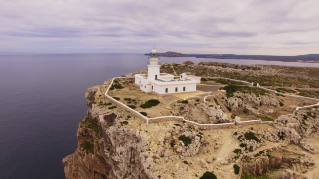 vídeos de stock e filmes b-roll de aerial footage recorded with drone flying over the cavalleria lighthouse of menorca in the north coast with nice cliff and nature wild. 4k uhd. - farol estrutura construída