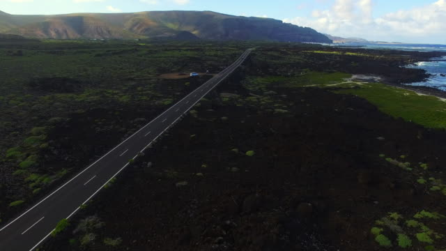 Aerial footage recorded with drone flying over the north coast of the beautiful volcanic island of Lanzarote with stunning landscape on the shoreline with long straight road. 4K UHD.