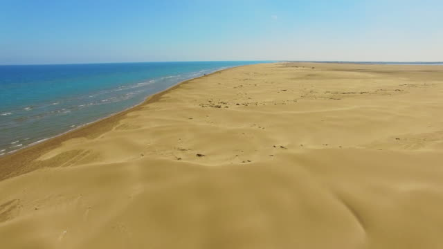 aerial footage recorded with drone flying over the stunning beach in the delta del ebro, a with beautiful sand dunes formations in the middle of the desert of the catalonia region. 4k uhd. - sand dune stock videos & royalty-free footage