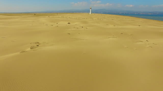 Aerial footage recorded with drone flying over the stunning beach in the Delta del Ebro, a with beautiful sand dunes formations with white lighthouse emerging in the middle of the desert of the Catalonia region. 4K UHD.