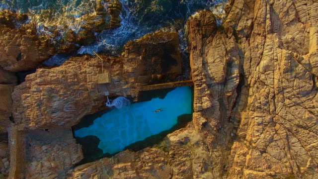 aerial footage recorded with drone flying over the stunning costa brava coast during sunrise with guy swimming in a nice swimming pool in the rocks close to mediterranean sea. 4k uhd. - rocky coastline stock videos & royalty-free footage