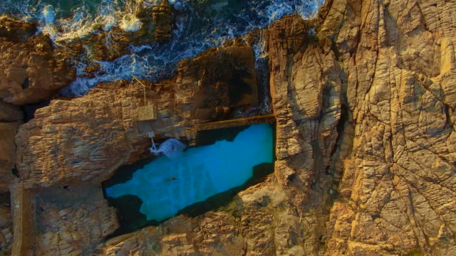 aerial footage recorded with drone flying over the stunning costa brava coast during sunrise with guy swimming in a nice swimming pool in the rocks close to mediterranean sea. 4k uhd. - one mid adult man only stock videos & royalty-free footage