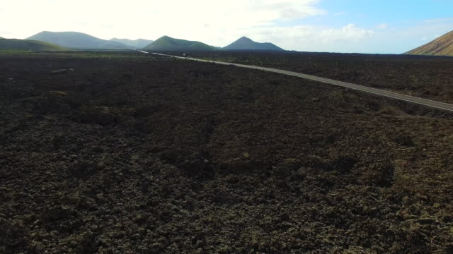 Aerial footage recorded with drone flying over the volcanic Lanzarote island with stunning volcano landscape and nice long straight road in the black land. 4K UHD.