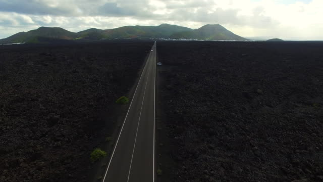 aerial footage recorded with drone flying over the volcanic lanzarote island with stunning volcano landscape and nice long straight road in the black land. 4k uhd. - 20 seconds or greater stock videos & royalty-free footage