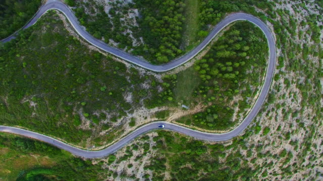 Aerial footage recorded with drone in a overhead view of a beautiful curved road in the Catalan Pyrenees mountains with car driving during a summer road trip. 4H UHD.