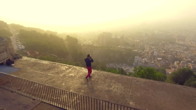 Aerial footage recorded with drone in the spanish civil war bunkers in top of Turo de la Rovira hill, guy contemplating the Barcelona city views on sunrise, this viewpoint has became a very popular place for tourists and locals for the 360º view.