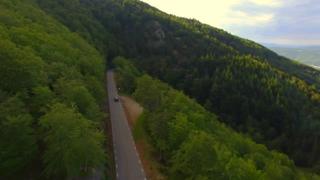 Aerial footage recorded with drone of a beautiful mountain road with nice curves in the Montseny natural reserve between woodland. 4K UHD.