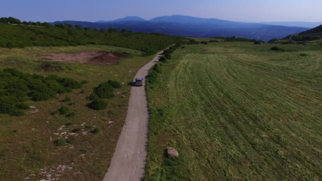 vídeos y material grabado en eventos de stock de aerial footage recorded with drone of a car driving on a mountain road in the nature fields during a trip in the catalan mountains. 4k uhd. - soleado