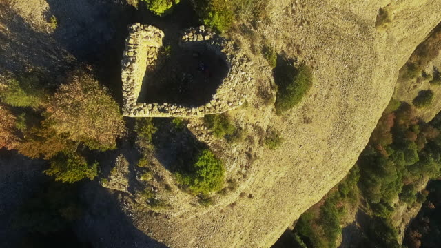 Aerial footage recorded with drone of a cenital view of a old chapel on top of mountain with guy walking and going inside in the Catalan Pyrenees.