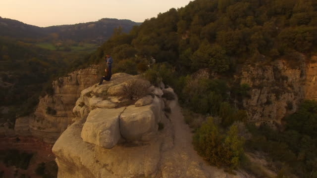 aerial footage recorded with drone of a couple in love sitting and hugging, contemplating the view from a stunning rocky viewpoint on sunset and the amazing landscape with cliffs in the catalonia region during a weekend hiking adventure. 4k uhd. - canyon stock-videos und b-roll-filmmaterial