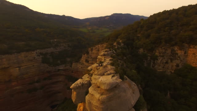 Aerial footage recorded with drone of a couple sitting and contemplating the view from a stunning rocky viewpoint on sunset and the amazing landscape with cliffs in the Catalonia region during a weekend hiking adventure. 4K UHD.