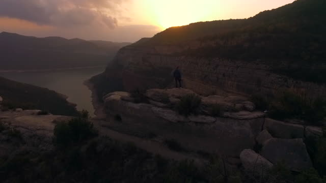 aerial footage recorded with drone of a guy contemplating and taking pictures of the view from a stunning rocky viewpoint on sunset and the amazing landscape with cliffs in the catalonia region during a weekend hiking adventure. - one mid adult man only stock videos & royalty-free footage