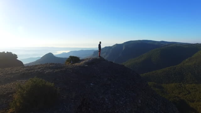 aerial footage recorded with drone of a guy on top of mountain contemplating the landscape and taking pictures in the catalan pyrenees mountains during a weekend trip. - on top of stock videos & royalty-free footage