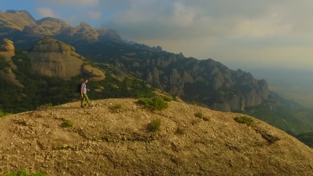 vidéos et rushes de aerial footage recorded with drone of a guy on top of summit mountain contemplating and taking pictures of the landscape in the montserrat mountains with his beautiful and unique formations in the catalonia region. - paysage enchanteur