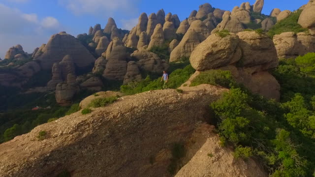 Aerial footage recorded with drone of a guy on top of summit mountain contemplating and taking pictures of the landscape in the Montserrat mountains with his beautiful and unique formations in the Catalonia region.