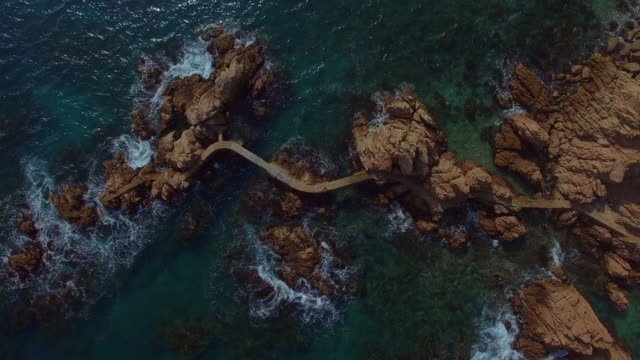 aerial footage recorded with drone of a nice corner of costa brava mediterranean sea with beautiful meandering path between the rocks over the water in the catalonia region. 4k uhd. - 30 sekunder eller längre bildbanksvideor och videomaterial från bakom kulisserna