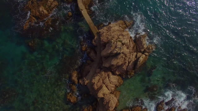 Aerial footage recorded with drone of a nice corner of Costa Brava Mediterranean Sea with beautiful meandering path between the rocks over the water in the Catalonia region. 4K UHD.