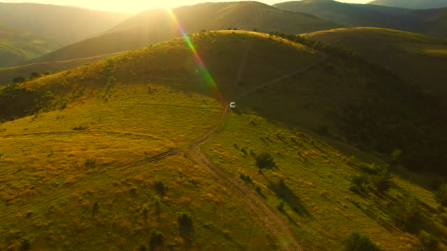 Aerial footage recorded with drone of a SUV 4x4 car driving off road in the beautiful mountains of the Catalan Pyrenees on sunset light during a summer road trip discovering amazing places. 4K UHD.