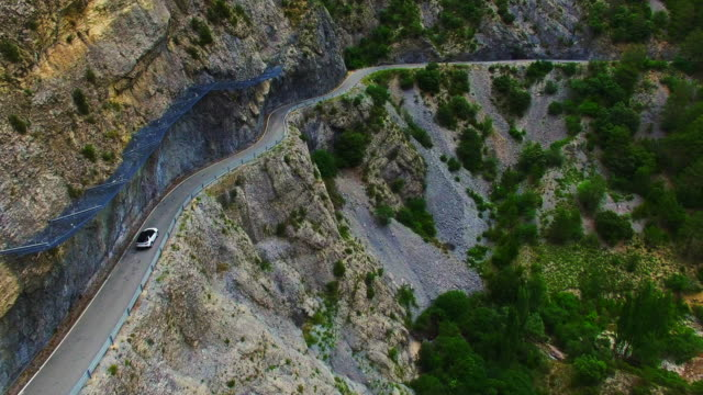 Aerial footage recorded with drone of a SUV 4x4 car driving through a mountain road in the Catalan Pyrenees during summer road trip between beautiful cliffs and tunnels. 4K UHD.