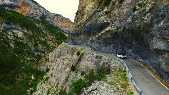 stockvideo's en b-roll-footage met aerial footage recorded with drone of a suv 4x4 car driving through a mountain road in the catalan pyrenees during summer road trip between beautiful cliffs and tunnels. 4k uhd. - sports utility vehicle