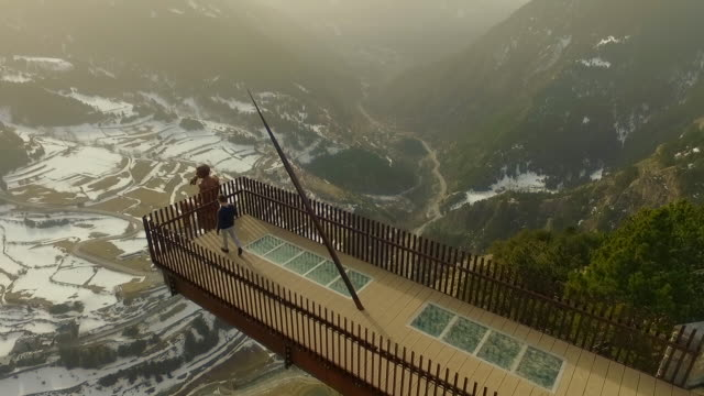 vidéos et rushes de aerial footage recorded with drone of a traveler guy walking and taking pictures over a nice walkway viewpoint over the andorra mountains with stunning landscape on winter. 4k uhd. - vertige