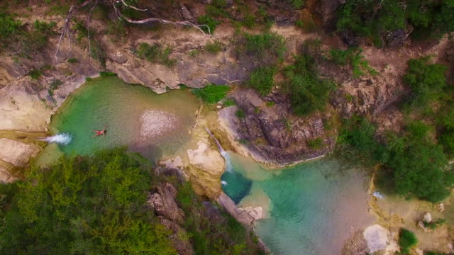 aerial footage recorded with drone of boy swimming during summer time in a green natural pools created in a river like an idyllic place of the catalan pyrenees. 4k uhd. - one teenage boy only stock videos & royalty-free footage