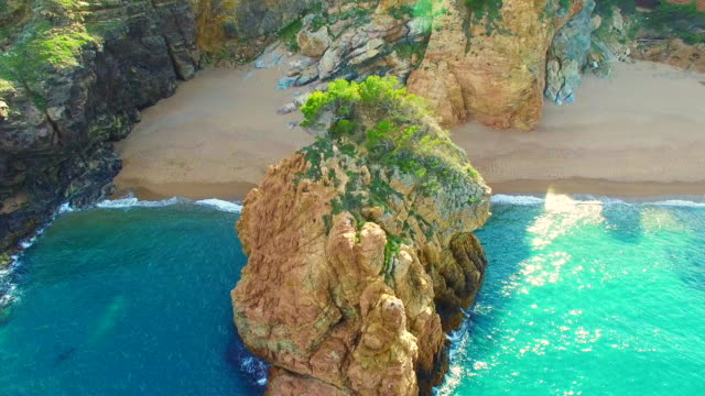vídeos de stock, filmes e b-roll de aerial footage recorded with drone of the beautiful and turquoise waters of costa brava shoreline with beautiful island and empty beach. - coluna de calcário marítimo