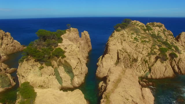 Aerial footage recorded with drone of the beautiful Costa Brava with green water and little beach between the rocky terrain and pine trees in a stunning landscape. 4K UHD.