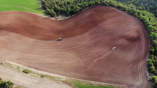 vídeos y material grabado en eventos de stock de aerial footage recorded with drone of tractor plowing the land in the countryside. - diseño natural