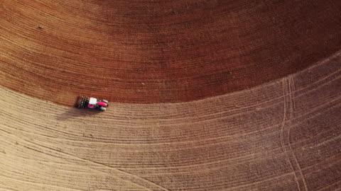 vídeos y material grabado en eventos de stock de aerial footage recorded with drone of tractor plowing the land in the countryside. - campo arado