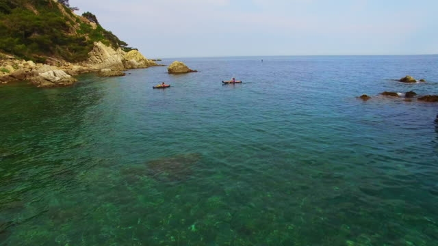 aerial footage recorded with drone of two girls practicing kayak in the mediterranean sea of costa brava on summer with clear and crystal waters in an idyllic place. 4k uhd. - nur mädchen stock-videos und b-roll-filmmaterial