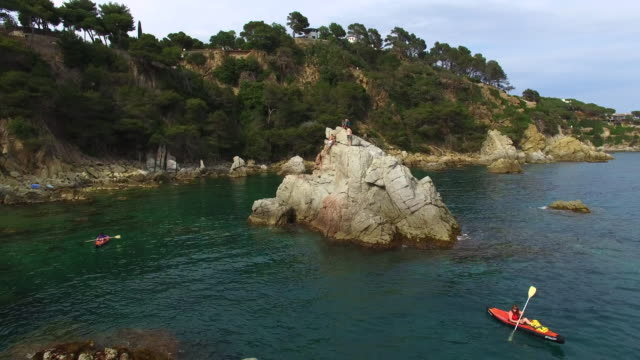 aerial footage recorded with drone of two girls practicing kayak in the mediterranean sea of costa brava on summer with clear and crystal waters in an idyllic place. 4k uhd. - カタルーニャ州点の映像素材/bロール
