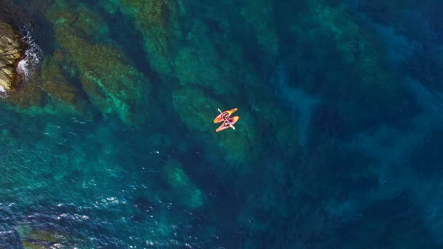 aerial footage recorded with drone of two girls practicing kayak in the mediterranean sea of costa brava on summer with clear and crystal waters in an idyllic place. 4k uhd. - water sport stock videos & royalty-free footage