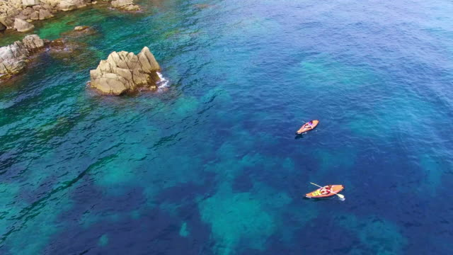 aerial footage recorded with drone of two girls practicing kayak in the mediterranean sea of costa brava on summer with clear and crystal waters in an idyllic place. 4k uhd. - turquoise coloured stock videos and b-roll footage