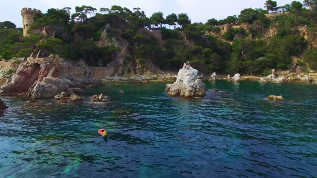 Aerial footage recorded with drone of two girls practicing kayak in the Mediterranean sea of Costa Brava on summer with clear and crystal waters in an idyllic place. 4K UHD.