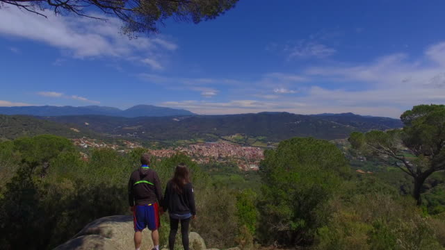 vídeos de stock e filmes b-roll de aerial footage recorded with drone passing by over a couple contemplating the views from viewpoint in the mediterranean region of catalonia. 4k uhd. - pine
