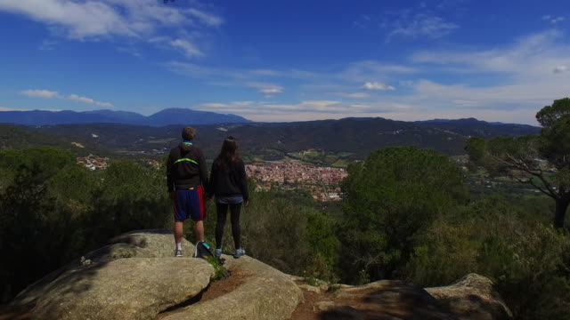 Aerial footage recorded with drone passing by over a couple contemplating the views from viewpoint in the Mediterranean region of Catalonia. 4K UHD.