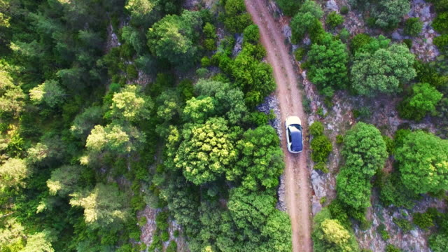 aerial footage recorded with drone with overhead view of suv 4x4 driving in a outdoor path in the catalan pyrenees during a summer travel. 4k uhd. - sports utility vehicle stock videos and b-roll footage