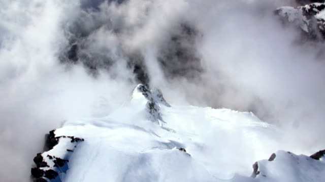 aerial footage spiral over high mountain and glacier in cloud - rock face stock videos and b-roll footage