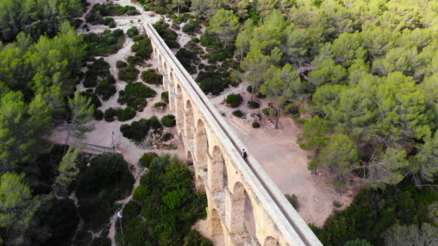 Aerial footage taken with drone of a guy crossing the beautiful Tarragona Roman bridge.