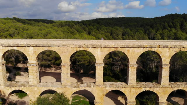 aerial footage taken with drone of a guy crossing the beautiful tarragona roman bridge. - old ruin stock videos & royalty-free footage
