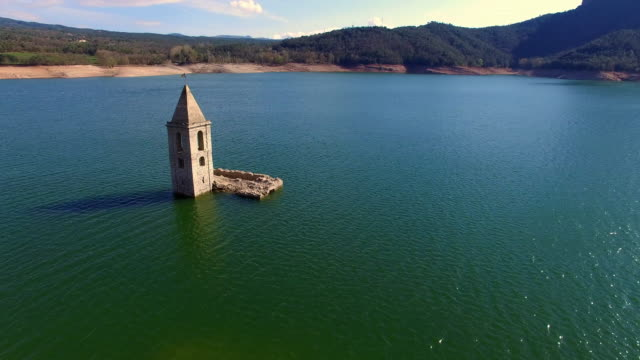 aerial footage view recorded with drone of the emergent church submerged into the waters of the sau reservoir in the catalonia region. 4k uhd. - reservoir stock videos and b-roll footage