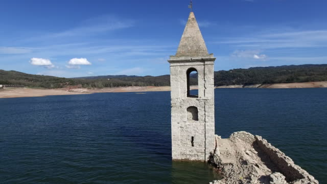 Aerial footage view recorded with drone of the emergent church submerged into the waters of the Sau reservoir in the Catalonia region. 4K UHD.